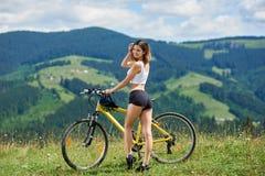 Молодая счастливая женщина задействуя на горном велосипеде на летнем дне стоковое фото