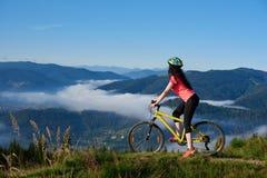 Молодая счастливая женщина задействуя на горном велосипеде на летнем дне стоковые изображения rf