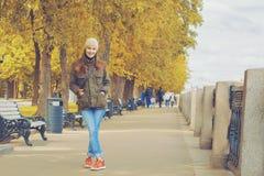 Молодая счастливая женщина идя в парк осени стоковые фотографии rf