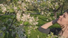 Молодая счастливая женщина идя в яблоневый сад весной цветет белизна Портрет красивейшей девушки акции видеоматериалы