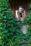 Молодая счастливая женщина на крылечке загородного дома среди растительности Стоковые Фото