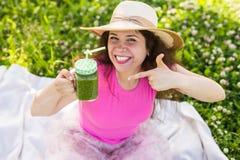 Молодая счастливая женщина показывает на зеленых smoothies на пикнике Здоровые еда, вытрезвитель и концепция диеты Стоковая Фотография RF