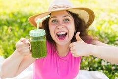 Молодая счастливая женщина показывая большие пальцы руки вверх с зелеными smoothies на пикнике Здоровые еда, вытрезвитель и конце Стоковая Фотография RF
