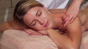 Молодая счастливая женщина получая ослабляя задний массаж на салоне сток-видео