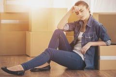 Молодая счастливая женщина сидит в комнате около коробок Двигать, приобретение нового жилья Стоковые Изображения