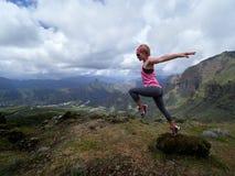 Молодая счастливая женщина скача na górze горы Стоковые Изображения