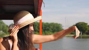Молодая счастливая женщина смешанной гонки туристская принимая фото Selfie используя мобильный телефон Усмехаясь девушка битника  видеоматериал
