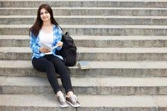 Молодая счастливая женщина студента при книги и рюкзак сидя на стоковые фото