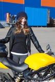 Молодая счастливая женщина с ее новым как раз поставленным мотоциклом в компании перевозки, получая велосипед Стоковое Изображение