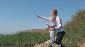 Молодая счастливая женщина с младенческим взглядом мальчика в расстояние и руку шоу в положение озера расстояния на камне в воде сток-видео