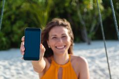 Молодая счастливая женщина усаженная на качание показывая вертикальный экран телефона Белые песок и джунгли как предпосылка стоковое фото