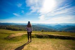 Молодая счастливая женщина na górze холма наслаждается красивым видом неба и гор Стоковые Фото