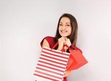 Молодая счастливая зубастая усмехаясь женщина с хозяйственными сумками Счастливые праздники Нового Года стоковые изображения