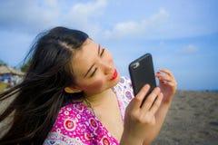 Молодая счастливая и красивая азиатская китайская женщина фотографируя selfie с камерой мобильного телефона на тропическом пляже  стоковые фото