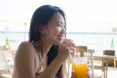 Молодая счастливая и красивая китайская азиатская женщина выпивая здоровый апельсиновый сок сидя на курорте пляжного ресторана на Стоковые Фотографии RF