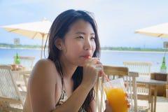 Молодая счастливая и красивая китайская азиатская женщина выпивая здоровый апельсиновый сок сидя на курорте пляжного ресторана на Стоковое Изображение