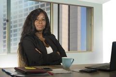 Молодая счастливая и привлекательная черная Афро-американская работа коммерсантки уверенно на усмехаться стола компьютера удовлет стоковое изображение