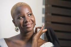 Молодая счастливая и привлекательная черная афро американская женщина при современная прическа представляя жизнерадостный и холод стоковое фото