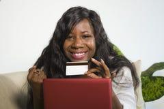 Молодая счастливая и привлекательная черная Афро-американская женщина используя банк кредитной карточки и ноутбука онлайн и ходя  стоковые фотографии rf