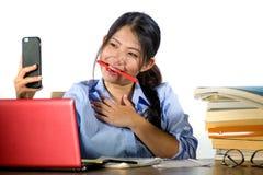 Молодая счастливая и успешная азиатская китайская девушка студента принимая фото автопортрета selfie с мобильным телефоном изучая стоковое изображение