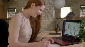 Молодая счастливая коммерсантка имбиря работает с компьтер-книжкой в офисе, сравнивает информацию с бумагами, концепцию работы акции видеоматериалы