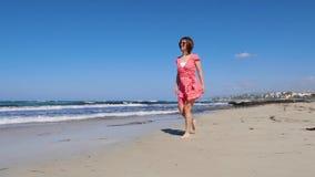 Молодая счастливая привлекательная женщина идя вдоль пляжа песка наслаждаясь солнцем Сильные волны и ветреная погода в Кипре ( сток-видео