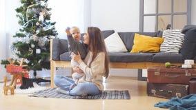 Молодая счастливая радостная семья Сын матери и ребёнка имея потеху около дерева рождества и Нового Года совместно дома, улыбка акции видеоматериалы