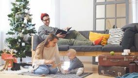 Молодая счастливая радостная семья Сын матери, отца и ребёнка одел в свитерах имея потеху около рождества и Нового Года видеоматериал