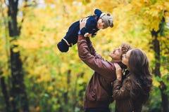 Молодая счастливая семья в осени в парке Отец joyfully бросает его сына вверх стоковое фото