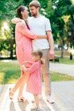 Молодая счастливая семья при маленький красивый младенец с голубыми глазами идя в парк лета на заходе солнца мама дочи маленькая Стоковая Фотография RF