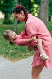 Молодая счастливая семья при маленький красивый младенец с голубыми глазами идя в парк лета на заходе солнца мама дочи маленькая Стоковые Фото