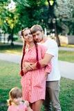 Молодая счастливая семья при маленький красивый младенец с голубыми глазами идя в парк лета на заходе солнца мама дочи маленькая Стоковые Фотографии RF