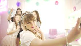 Молодая счастливая excited привлекательная белокурая женщина принимая фотоснимок телефона selfie с женским другом в предпосылке видеоматериал