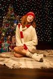 Молодая ся женщина сидя около рождественской елки Стоковое Фото