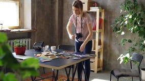 Молодая творческая девушка делает квартиру положенную из красочных фото, после этого снимая их с камерой Женщина стоит близко видеоматериал
