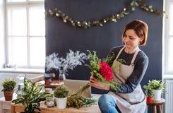 Молодая творческая женщина в цветочном магазине r стоковое фото