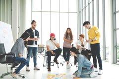 Молодая творческая разнообразная групповая встреча и смотреть план проекта положенный вне на пол обсуждают или коллективно обсужд стоковые фотографии rf