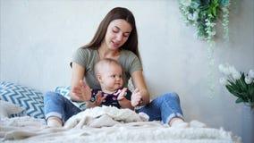 Молодая темн-с волосами девушка матери и младенца сидит на кровати и хлопать акции видеоматериалы