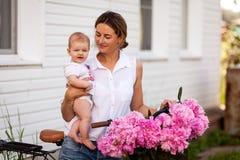 Молодая темн-с волосами женщина с младенцем и пионами стоковые фотографии rf