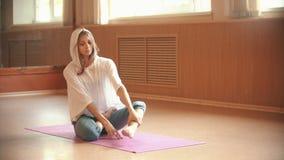 Молодая тонкая женщина сидя на циновке йоги и кладет ее ноги в положение лотоса сток-видео