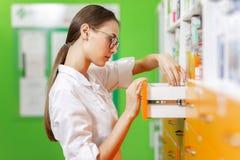 Молодая тонкая коричнев-с волосами девушка со стеклами, одетыми в медицинской прозодежде, готовит шкафчик и ищет что-то стоковые изображения