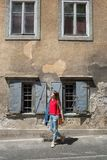 Молодая туристская девушка идет маленьким городом улицы a в горах Словении, Европы Затрапезные старые фасады домов, и Стоковое Изображение RF