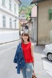 Молодая туристская девушка идет маленьким городом улицы a в горах Словении, Европы Затрапезные старые фасады домов, и Стоковое Изображение