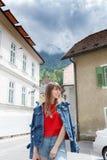 Молодая туристская девушка идет маленьким городом улицы a в горах Словении, Европы Затрапезные старые фасады домов, и Стоковое Фото