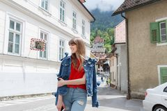 Молодая туристская девушка идет маленьким городом улицы a в горах Словении, Европы Затрапезные старые фасады домов, и Стоковые Изображения