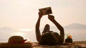 Молодая туристская девушка используя передвижное устройство таблетки и загорающ на тропическом пляже рая 4K, Slowmotion Пхукет сток-видео