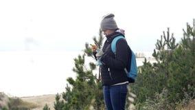 Молодая туристская девушка, стоя на высоком банке озера, смотрит что-то в телефоне slowmotion, HD, 1920x1080 видеоматериал