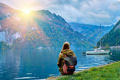 Молодая туристская девушка с рюкзаком смотря красивый сценарный восход солнца на австрийском озере горных вершин Перемещение битн стоковое фото