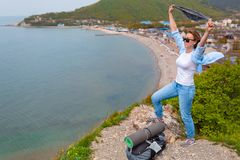 Молодая туристская женщина взобралась к верхней части горы Эмоции утехи и счастья Гора и море на заднем плане Экземпляр стоковые изображения