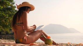 Молодая туристская женщина в бикини используя передвижное устройство таблетки и сидеть на тропическом песчаном пляже рая 4K, Slow видеоматериал